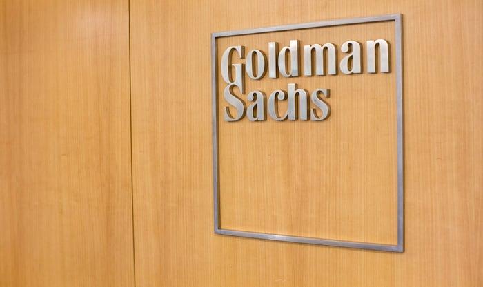 Goldman Sachs logo on a wooden wall.