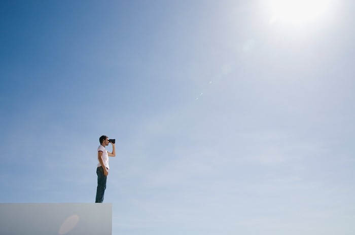 A person on a ledge looks through binoculars over an abyss with the sun shining down.