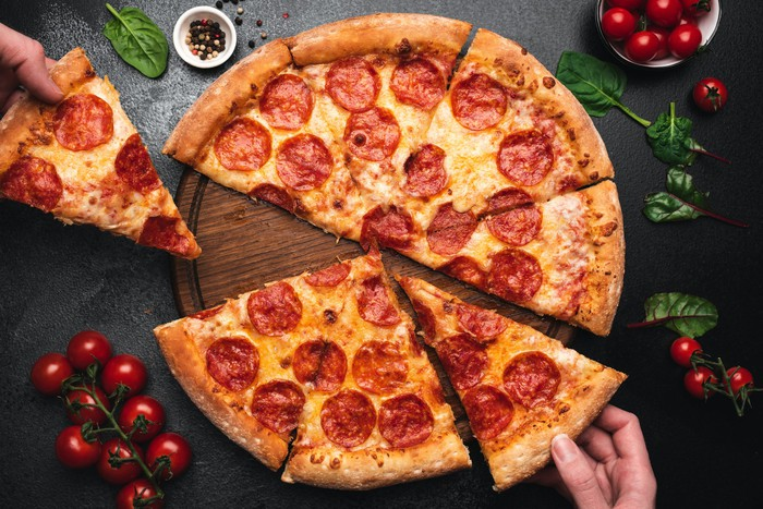 Pepperoni pizza cut into eight slices, with hand taking one away