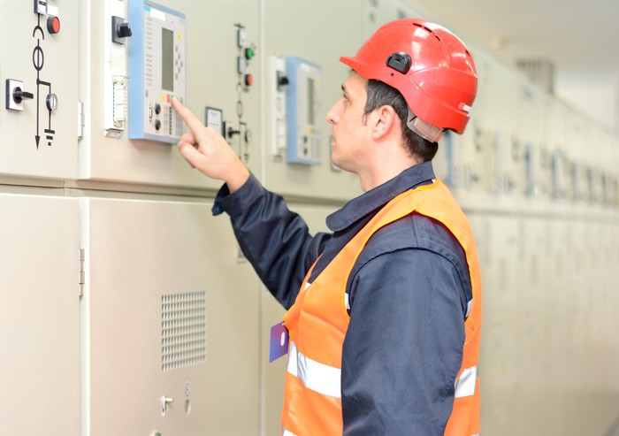 A man checking on electric industrial equipment