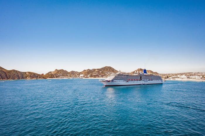 A cruise ship docked near an island.