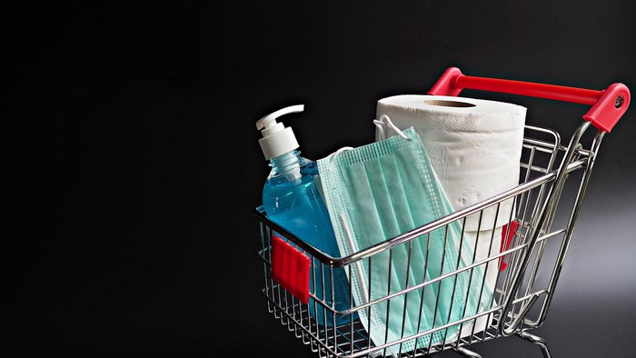 A shopping cart filled with toilet paper, sanitizer, and a mask