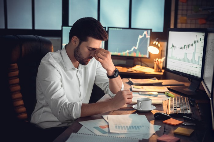Frustrated trader with his head down at his desk with monitors showing charts in the background.