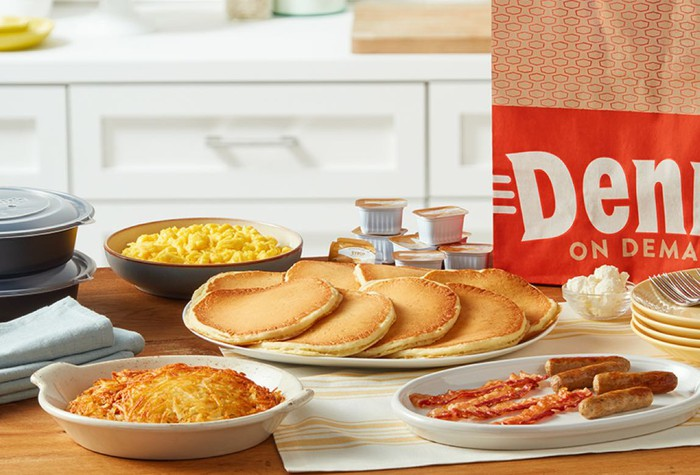 A Denny's shareable family pack of breakfast foods sitting on a table.