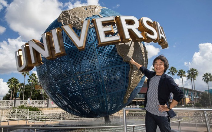 A tourist stands in front of the Universal globe logo at Universal Orlando.