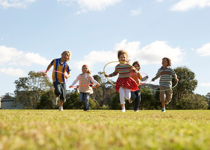 Five children with hula hoops running through a grass field, with trees and sky behind.