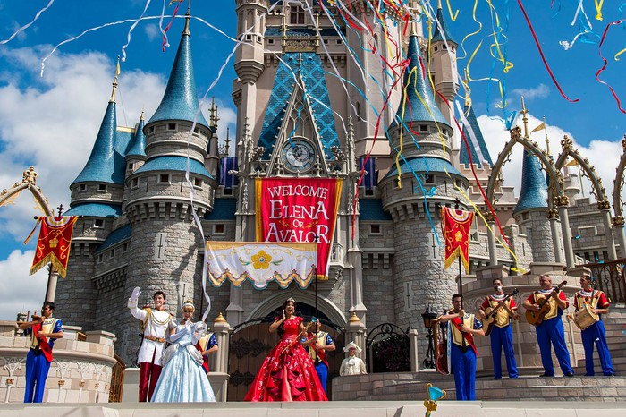 Magic Kingdom at Disney, with several characters in front and lots of streamers flying through the sky.