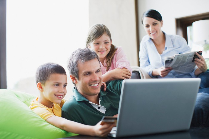 A family huddled around a laptop smiling while making an online purchase.