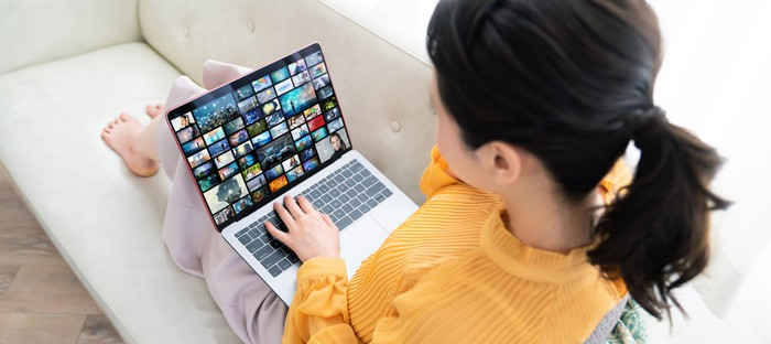 A woman with bare feet sitting on a couch, while looking at streaming video options on a laptop.
