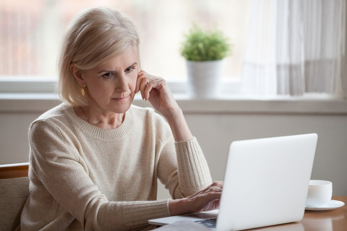 Older woman with serious expression at laptop