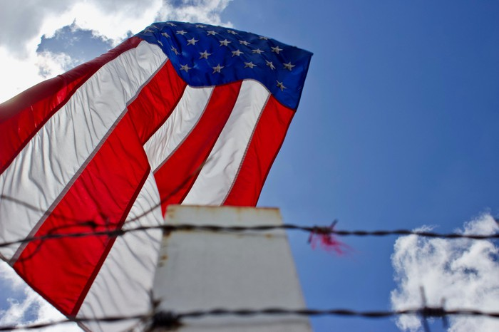A barbed-wire fence in the foreground, with an American flag waving behind it.