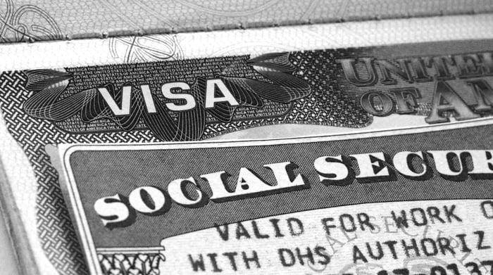 A Social Security card laid atop a work visa.