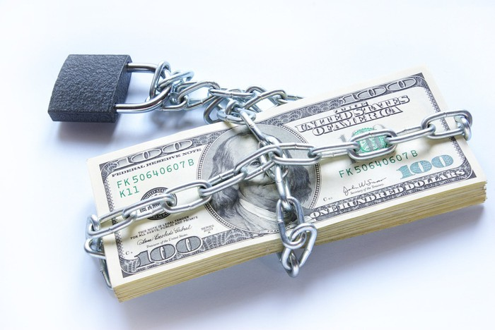 A neat stack of one hundred dollar bills wrapped up by thick chain that's locked into place.