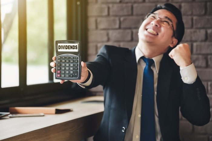 A smiling businessman pumps his fist, holding up a calculator where the display reads DIVIDENDS.