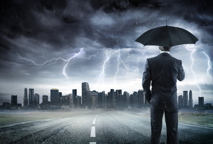 A businessman holds an umbrella over hs head looking on at a cityscape under an intense lightning storm.