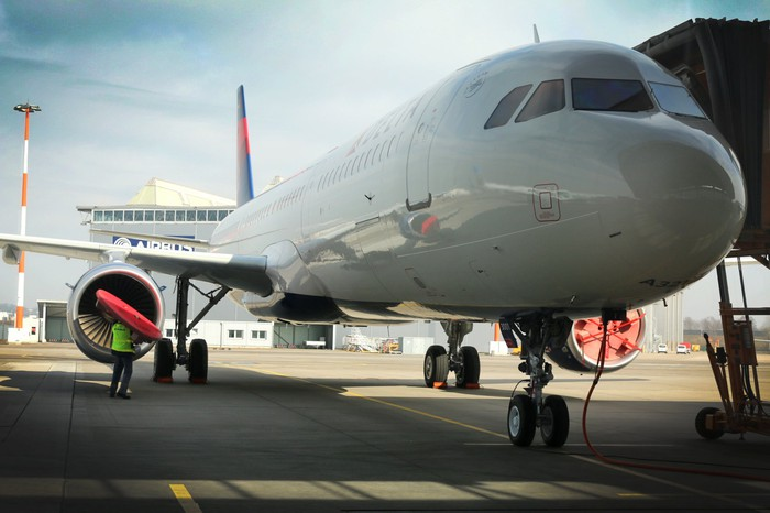 A Delta Airbus A321 at an airport terminal gate.