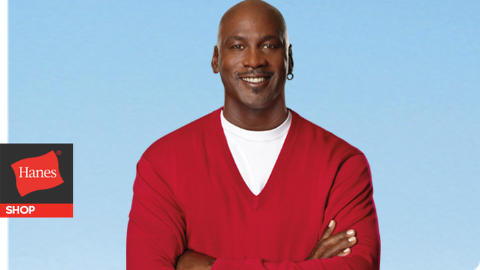 Michael Jordan smiling in a hanes T-shirt and sweater.