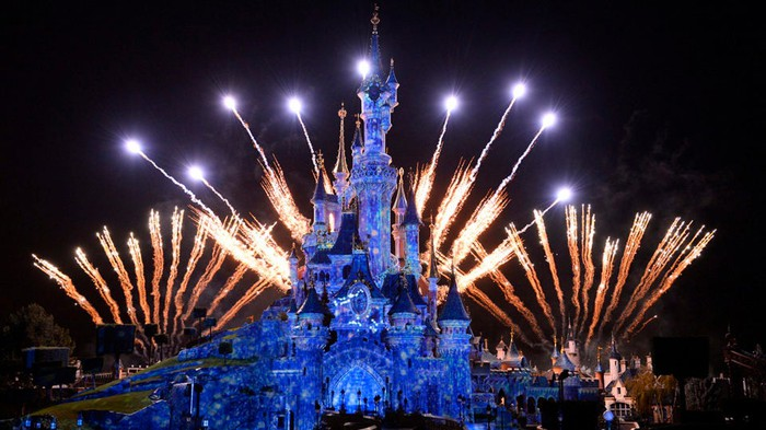 Disney theme park castle with fireworks at night