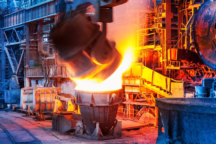 Ladle pouring molten steel during steelmaking process.