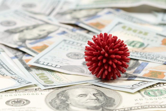 A red coronavirus model on top of a messy pile of $100 bills