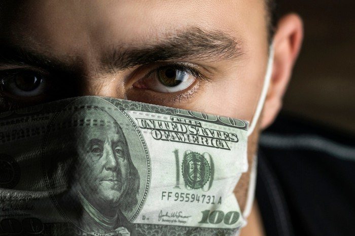 Man wearing mask that looks like a $100 bill