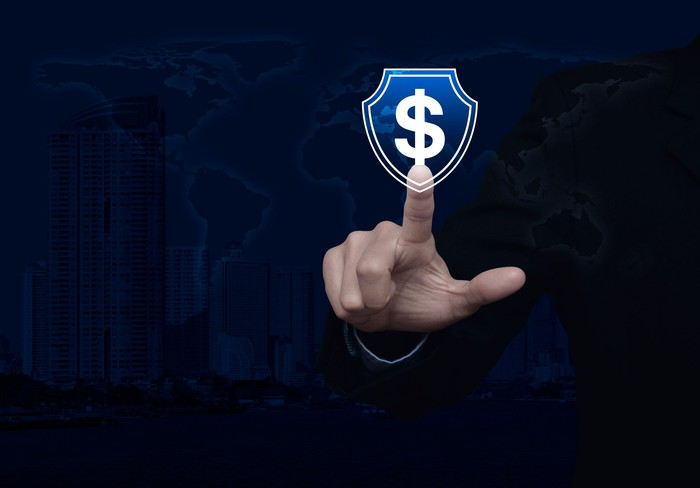 Finger pointing to dollar sign in a shield outline