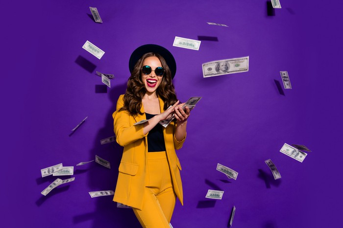 A young hipster woman in sunglasses and a hat makes it rain tossing hundred dollar bills everywhere against a purple background.