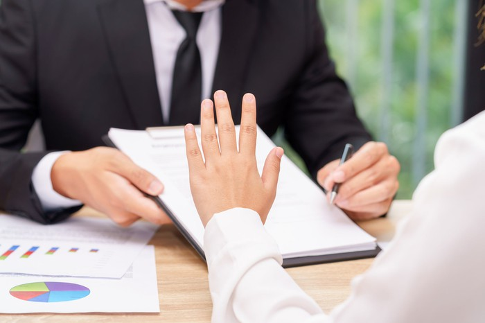 A businessperson refuses a contract.