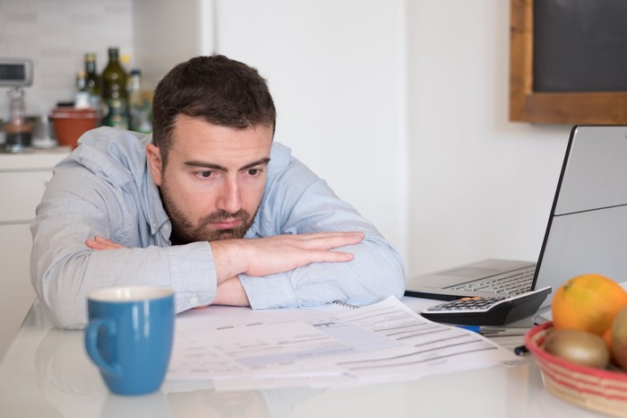 Man leaning over at table with papers, mug, calculator, and laptop