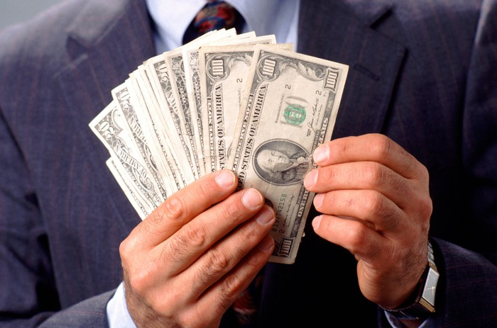 Man in business suit holding a wad one hundred dollar and twenty dollar bills.