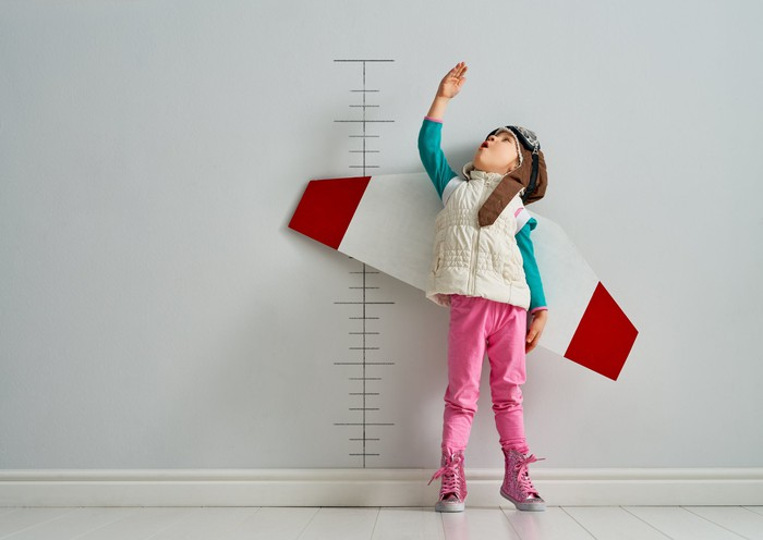 A kid wearing paper wings measuring herself against a ruler drawn on a wall.