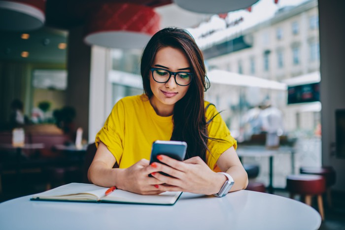 Young woman in glasses staring at her smartphone.