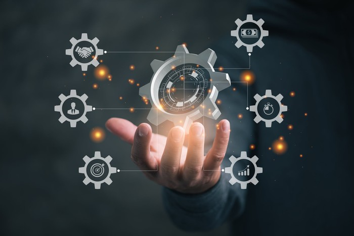 Concept art of business efficiency showing a businessman's hand touching a network of electronic gears.