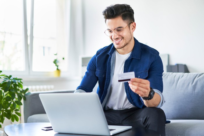 Man holding credit card and smiling while looking at laptop