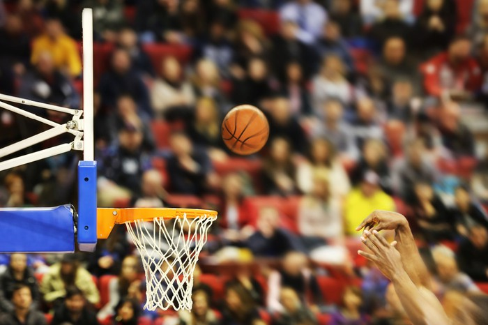 A basketball hovers over the basket as a player makes a shot.