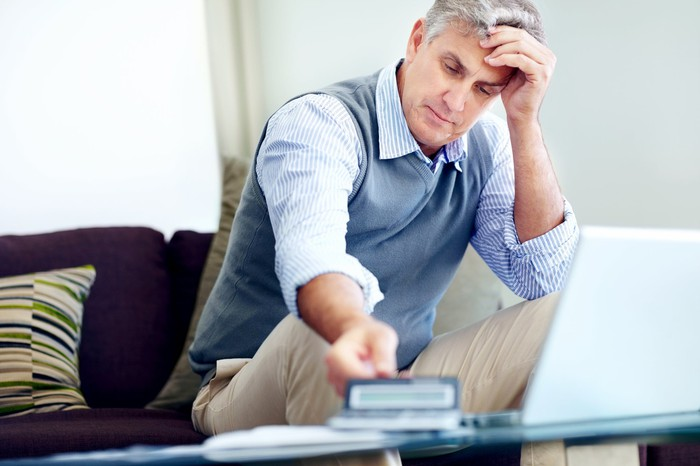 Older man sitting on couch holding his head, with laptop on table in front of him