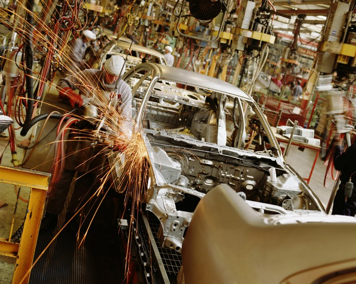 auto assembly line worker welding on auto frame