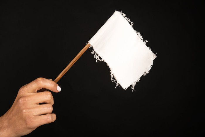A hand holds up a small, rugged white flag on a black backdrop.