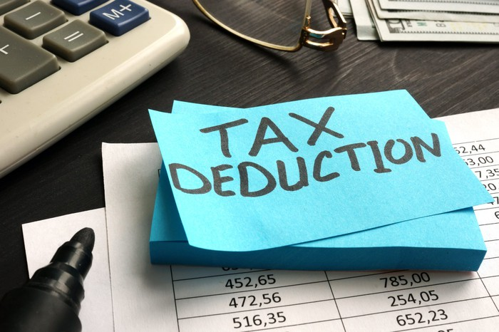 "A blue sticky note pad with the words ""Tax Deduction"" written on the top one."