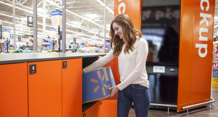 A Walmart shopper retrieves a package from a Walmart pick-up tower