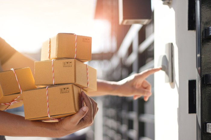 A delivery person holding several boxes rings the doorbell at a home.