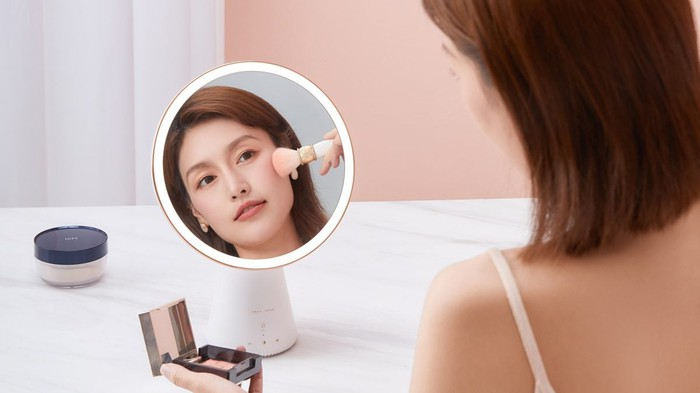 A Chinese woman applies makeup with the help of a Tmall Genie Queen smart mirror.