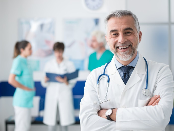 Male healthcare provider standing with his arms crossed, smiling. One male and two female healthcare workers are in the background.