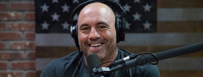 Joe Rogan wearing headphones behind a microphone.