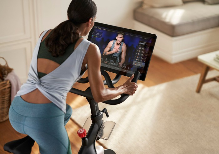 A woman is exercising while watching a workout class on a Peloton connected exercise bike.