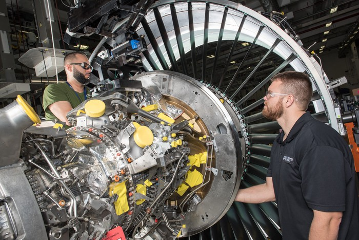 Two Pratt & Whitney employees work on an aircraft engine.