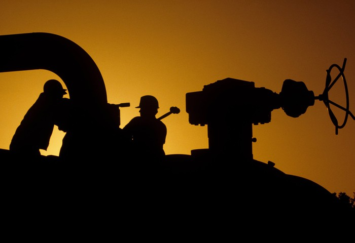 Silhouette of workers operating on a pipeline at sunset.