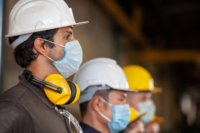 factory workers wearing ppe including face masks