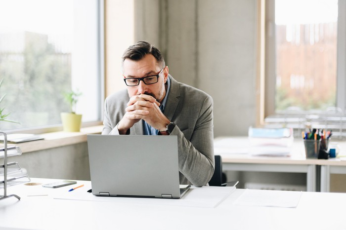 A man sits thoughtfully in front of a laptop at his desk.