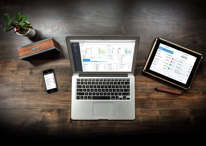The Shopify app shown on a laptop, smartphone, and tablet, which are all sitting on a wooden desk.